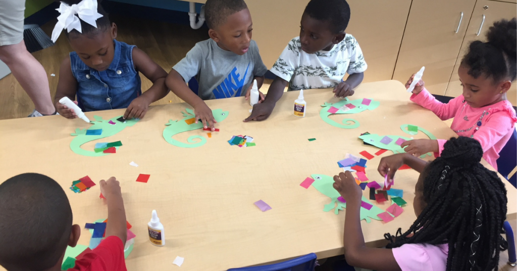 Six young children sit around a short table doing activities together, now that the CHILD Center is open.