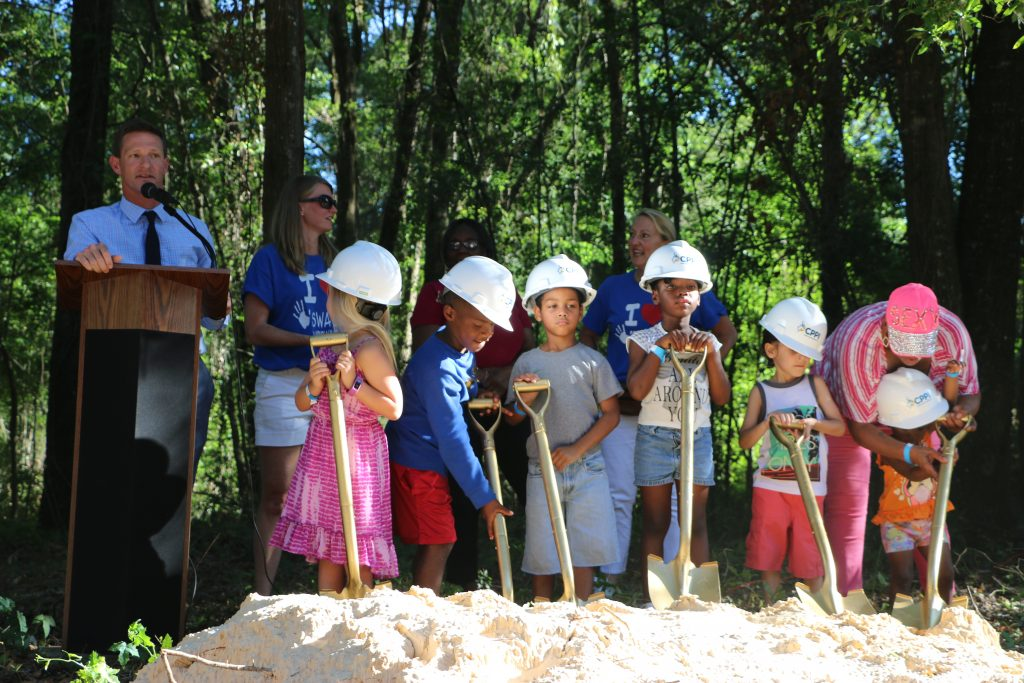 Six children stand with shovels, ready to dig during the celebration of breaking ground for the CHILD Center facility.