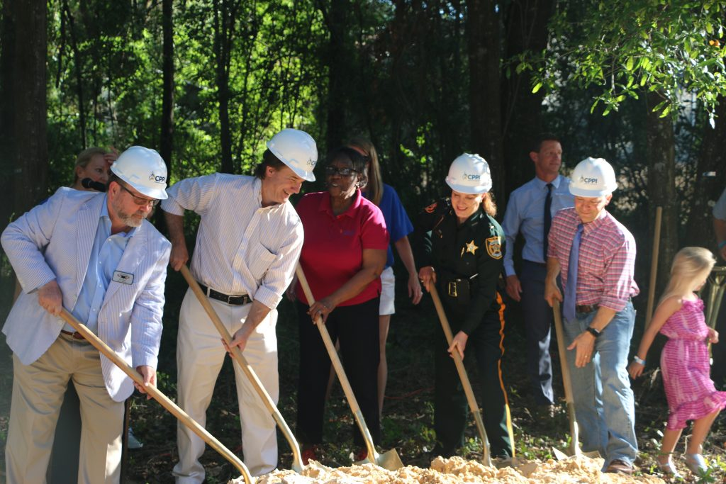 Five adult community members dig together at the site of the future CHILD Center facility during the ground breaking.