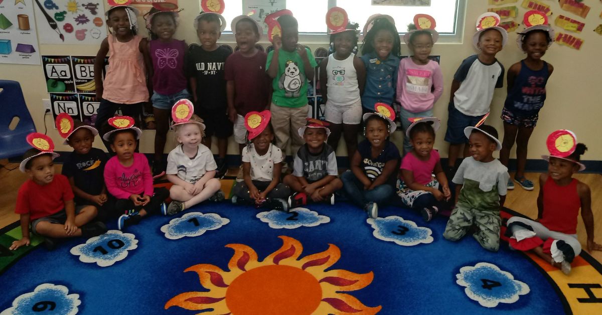 The CHILD Center's first class of students stands and sits on a circular rug in their classroom.