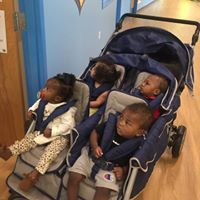Four young children share a stroller inside the CHILD Center, which is now open.