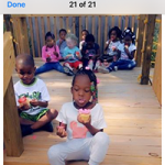 Nine children sit outside the open CHILD Center eating snacks in the play area.