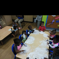 Six young children sit around a short table crafting with clay, now that the CHILD Center is open.