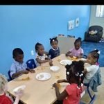 Seven children eat together around a short table inside the CHILD Center.