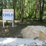 """A sign reading """"Coming 2018: CHILD Center for Early Learning"""" stands next to a large dirt pile."""