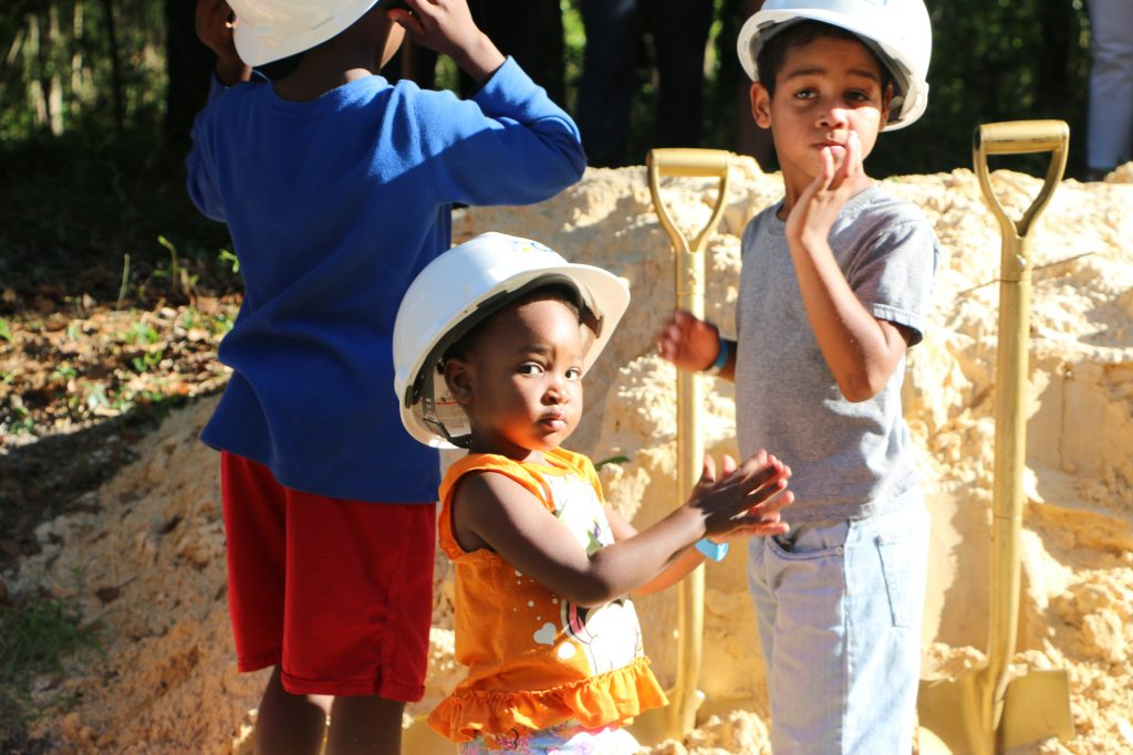 Three children wearing construction hats prepare to break ground for the CHILD Center facility.