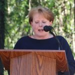 A person gives a speech from an outdoor podium during the celebration of breaking ground for the CHILD Center.