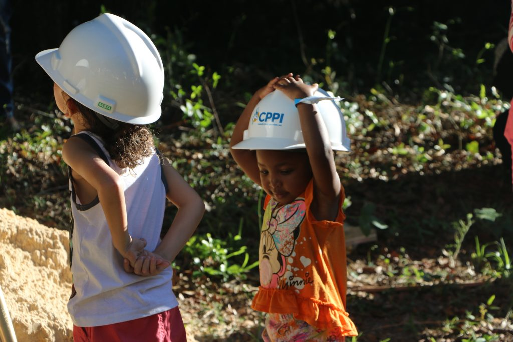 Two small children prepare to dig with shovels. The smaller of the two excitedly holds her construction hat to her head.