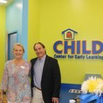 Dorothy Benson and another community member standing next to the CHILD Center logo displayed on a wall.