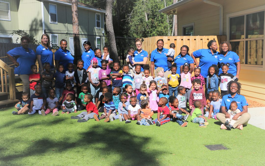 The inaugural class of students at the CHILD Center sits on the grass in front of a row of smiling instructors.