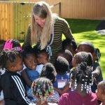 Dorothy Thomas smiles animatedly at a group of children grouped around her.