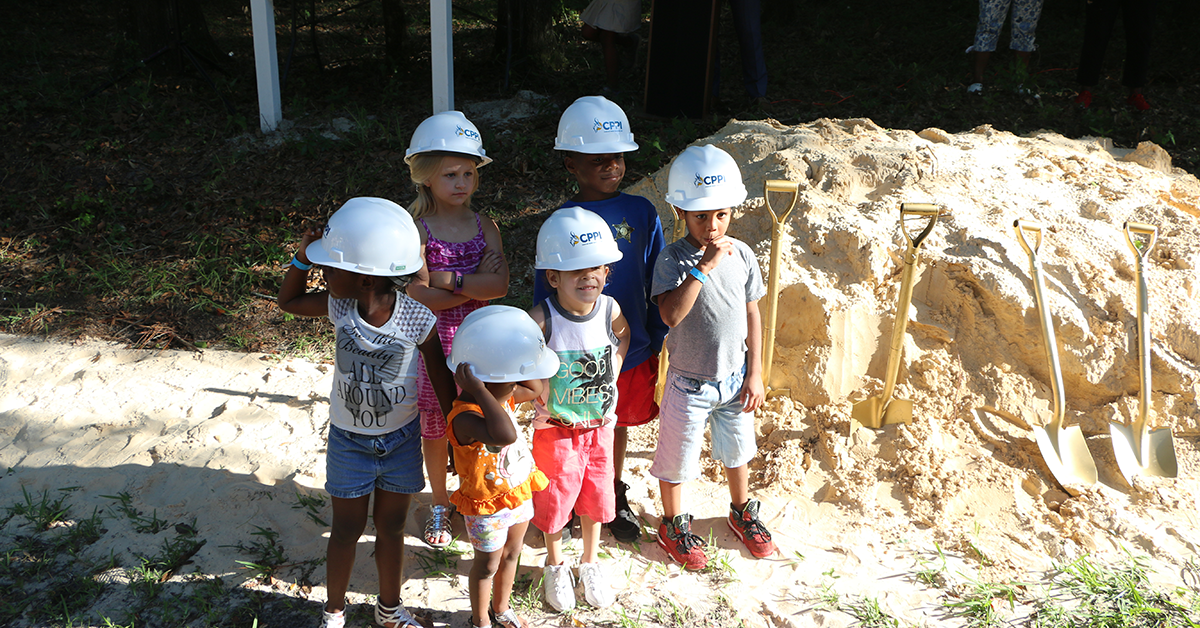 """Six children wearing construction hats stand next to a large mound of dirt and a """"Coming Soon"""" sign for the CHILD Center."""