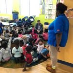 A CHILD Center instructor overseeing a group of young children sitting on the floor during a visit by special guests