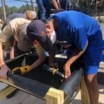 Two men in tee shirts and baseball caps use drills to secure a lining inside the raised garden beds for the CHILD Center