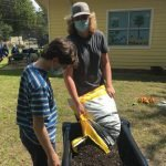 Two members of a team of Boy Scouts empty soil into a newly constructed garden bed