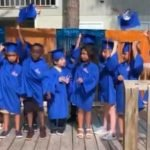 The class of 2020 wear graduation regalia and toss their hats into the air