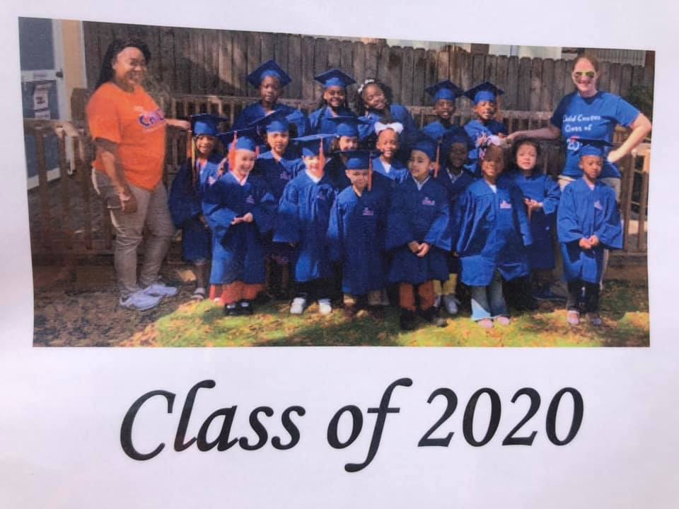 The class of 2020 wears blue graduation regalia and poses together for a photo