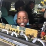 A CHILD Center graduate smiles out the window of a car