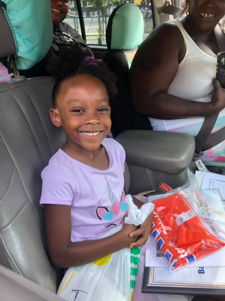 A CHILD Center graduate smiles out the window of a car, holding graduation gifts