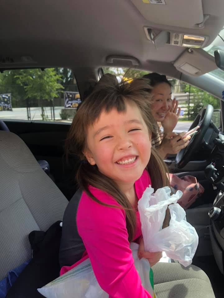 A 2020 CHILD Center grad smiles out the window of a car