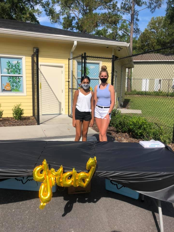 """Two young ladies stand behind a table with a balloon reading """"grad"""""""