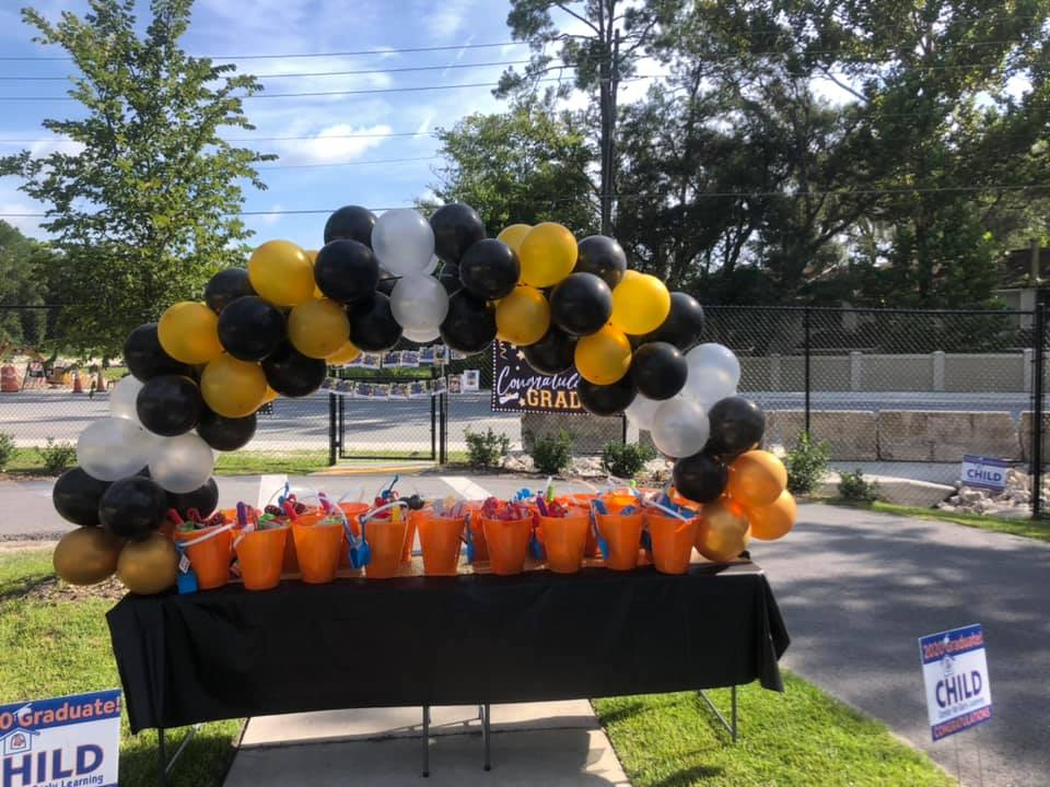 Gift baskets for the 2020 CHILD Center graduates are arranged under a decorative balloon arch