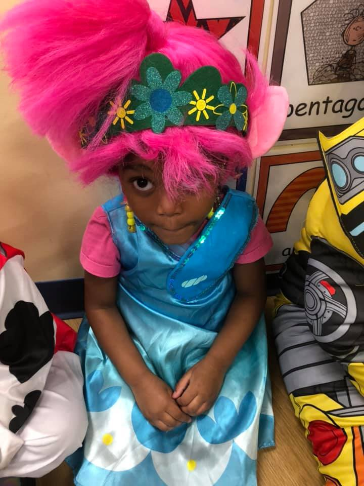 A CHILD Center student wearing a costume featuring a hot pink wig and blue dress