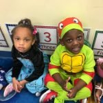 Two CHILD Center students wearing Halloween costumes