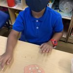 A CHILD Center student wearing a face mask makes pumpkin slime