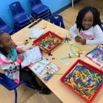Two young children smiling at the camera while doing an activity together at a table inside the CHILD Center